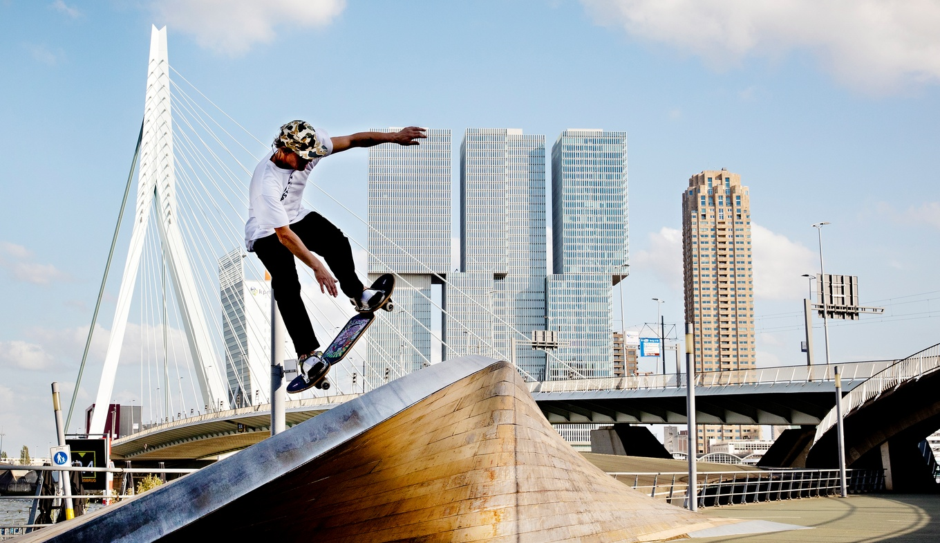 Skateboarder makes move with Rotterdam skyline background